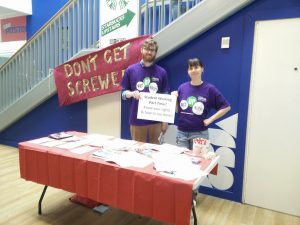 Two people stand behind a UNISON stall, in front of a banner saying 'Don't get screwed'